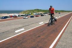 Senior man cycling on Dutch seawall Brouwersdam Stock Images