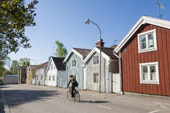 Senior man cycling by wooden houses Royalty Free Stock Photography