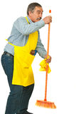 Senior man dancing with broom. Senior cleaning man dancing with broom islated on white background Royalty Free Stock Image