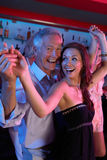 Senior Man Dancing With Younger Woman In Busy Bar. Senior Man Dancing With Younger Woman Happily In A Busy Bar royalty free stock photo