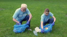 Senior man and daughter cleaning park, collecting garbage bag giving high five. Stock footage stock video footage