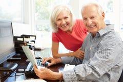 Senior man and daughter using computer at home Stock Image