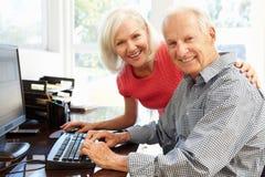 Senior man and daughter using computer at home Royalty Free Stock Image