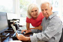 Senior man and daughter using computer at home Stock Images
