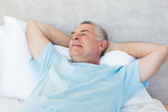 Senior man day dreaming in bed Royalty Free Stock Images