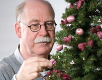 Senior man decorate Christmas tree Stock Photos
