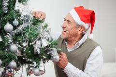 Senior Man Decorating Christmas Tree Royalty Free Stock Photography