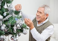 Senior Man Decorating Christmas Tree Royalty Free Stock Photo