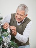 Senior Man Decorating Christmas Tree Stock Photo