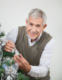 Senior Man Decorating Christmas Tree Stock Images