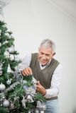 Senior Man Decorating Christmas Tree With Silver Stock Photo