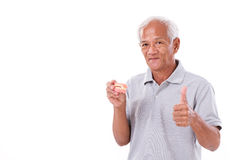 Senior man with denture, giving thumb up Royalty Free Stock Images