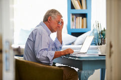 Senior Man At Desk Working In Home Office With Laptop Royalty Free Stock Image