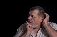 Senior man desperately thinking about life problems in the darkness Stock Photos
