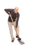 Senior man digging with a shovel. Full length portrait of a senior man digging with a shovel and looking at the camera isolated on white background Stock Photo