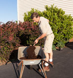 Senior man digging soil in wheelbarrow Stock Photography