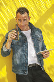 Senior man with digital tablet and beer on a yellow wall. Stock Photo