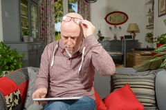 A senior man with a digital tablet. On the sofa stock photo