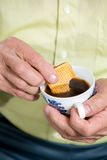 Senior man dips a cookie in his coffee Stock Images