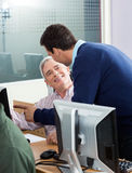 Senior Man Discussing With Instructor In Computer Class Royalty Free Stock Image