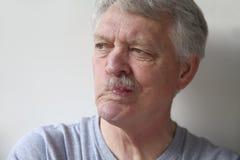 Senior man distorts his mouth Royalty Free Stock Photo