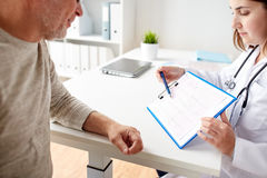 Senior man and doctor with cardiogram at hospital Stock Images