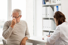 Senior man and doctor meeting at hospital Stock Photos