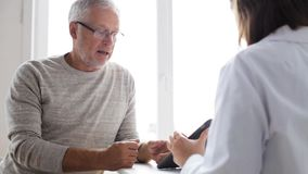 Senior man and doctor with tablet pc at hospital 51. Medicine, age, health care and people concept - senior man and doctor with tablet pc computer meeting in stock footage