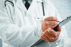 Senior man doctor writes medical records Stock Images
