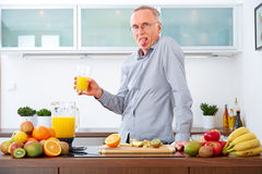 Senior man does not like to drink his Juice Royalty Free Stock Image