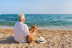 Senior man with dog at the beach Royalty Free Stock Photo