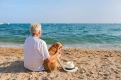 Senior man with dog at the beach Royalty Free Stock Photo