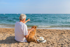 Senior man with dog at the beach Royalty Free Stock Photography