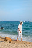 Senior man with dog at the beach. Senior man with dog in white suit walking at the beach royalty free stock image