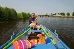 Senior man with dog in boat. Senior man with dog in little rowingboat at Dutch river Stock Photos