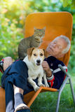 Senior man with dog and cat. Senior man sleeping in sunbed in courtyard while dog and cat sitting in his lap Royalty Free Stock Photography