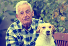 Senior man with dog in courtyard Stock Images