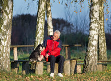 Senior man with dog in the park. Senior man with Miniature schnauzer sitting on bench in the park stock photos
