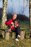 Senior man with dog in the park. Senior man sitting on bench in the park and hugging his cute dog royalty free stock images