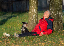 Senior man with dog sitting in forest. Senior man sitting on the ground leaning on tree and keep eyes closed while his dog Miniature schnauzer looking at him stock images