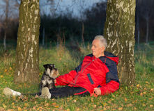 Senior man with dog sitting in forest. Senior man with his dog Miniature schnauzer sitting on grass in the forest royalty free stock photography