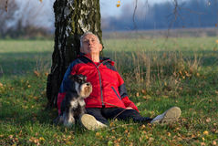 Senior man with dog sitting in forest. Senior man with his dog Miniature schnauzer sitting on the ground and leaning on the tree in the park stock image