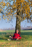 Senior man with dog sitting on grass leaning on tree. Senior man with his dog Miniature schnauzer sitting on grass leaning on birch tree with yellow leaves royalty free stock images