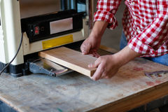Senior man doing carpentry with edging plane on workbench Royalty Free Stock Photography