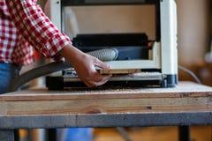 Senior man doing carpentry with edging plane on workbench Stock Photos