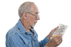 Senior man doing crossword. Senior man puzzling over a clue in the crossword stock images
