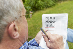 Senior Man Doing Crossword Puzzle In Garden Stock Photo