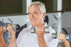 Senior man doing dumbbell training Stock Photo