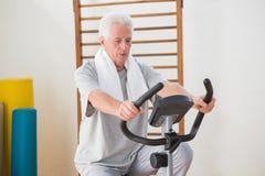 Senior man doing exercise bike Stock Photos