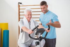 Senior man doing exercise bike with his trainer. Senior men doing exercise bike with his trainer in fitness studio Royalty Free Stock Photography